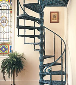 blue spiral staircase in cream hall and stained glass window, via Must Know How